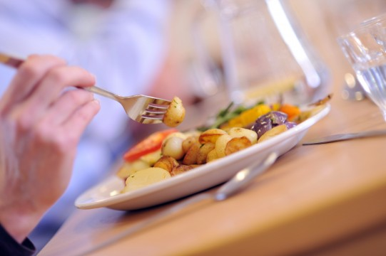 hand holding fork over plate of food
